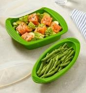 Two silicone steam cookers being used to prepare green beans and a dish of salmon and vegetables
