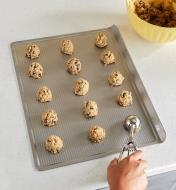 EV690 - Scooping raw cookie dough onto a cookie sheet