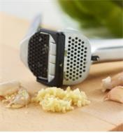 Crushed garlic and peel on a cutting board with the Garject Garlic Press