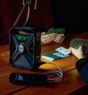 Lumière de la radio météo d'urgence Eton utilisée pour jouer aux cartes tout en rechargeant un téléphone cellulaire