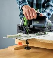 Cutting particleboard with a track saw on a track-saw guide held in place by track-saw guide clamps