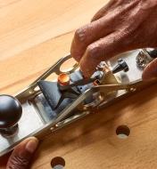 Personne relevant le levier du mécanisme de blocage pour changer la lame d'un rabot d'atelier à double tranchant