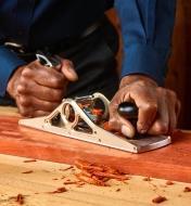Rabot d'atelier à double tranchant utilisé avec un biseau de 35° pour effectuer la finition d'une pièce de padouk