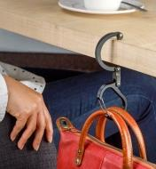 A Heroclip carabiner used to hang a purse on the edge of a table in a restaurant
