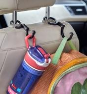 Two Heroclip carabiners used to hang a water bottle and a backpack on the back of a car seat