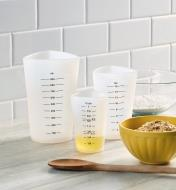 Three sizes of flexible silicone measuring cups on a countertop with the liquid level in the smallest size clearly visible through the side