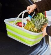 Personne déposant un panier compressible rempli de provisions dans le coffre d'une voiture