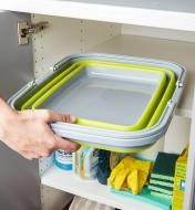 Collapsible tote collapses to fit into a cupboard