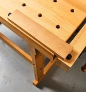 A block of wood clamped using dog holes in the vise and bench top
