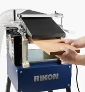 "A woodworker feeds stock into the Rikon 10"" helical planer/jointer"
