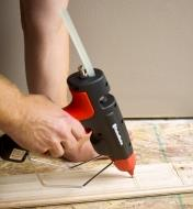 A FastenMaster pro hot-melt gun being used to apply glue to a piece of wooden flooring