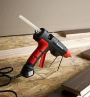A FastenMaster pro hot-melt gun resting on its stand during a flooring installation project
