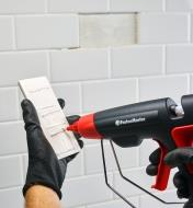 Replacing a missing tile, using the FastenMaster pro hot-melt gun to glue a new tile in place