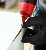 Using the FastenMaster pro hot-melt gun repair nozzle to inject glue under a section of lifted edge trim