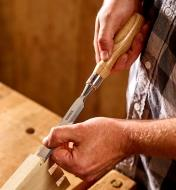 "A woodworker uses a 3/4"" Narex Richter chisel to trim the tails of a large dovetail joint"