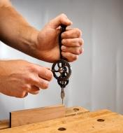 Drilling a hole in the edge of a board with the replica egg-beater drill