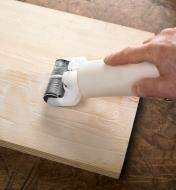 Spreading glue onto a board with the Roller Glue Applicator
