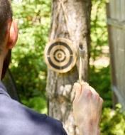 Homme visant la cible en bois pendant une partie du jeu de lancer de haches miniatures