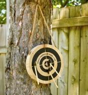 Trois haches miniatures plantées dans une cible en bois suspendue à un arbre