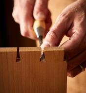 Using a Japanese dovetail chisel to clean out the bottom of a pin socket on a dovetail joint