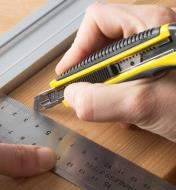 Using a square to cut a line in wood with a pencil blade