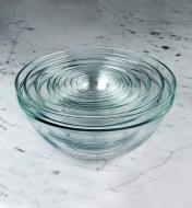 A set of nine Duralex glass bowls sitting on a countertop, nested for compact storage