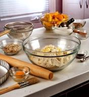 Various sizes of Duralex glass bowls being used to contain and mix ingredients to make a peach pie