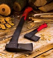 The splitting axe and the hatchet lying near some firewood and kindling