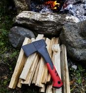 The hatchet lying on a pile of kindling beside a campfire