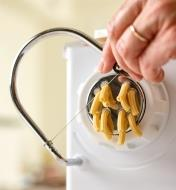 Using the slicer included with the pasta extruder to cut homemade macaroni to the desired length