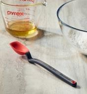 The mini spoon-spatula on a countertop near a glass measuring cup and mixing bowl