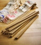 Pile of 10 wenge chopstick blanks with bags in the background