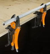 Two pairs of Grip-On locking pliers set in job-site holders for use as vises to hold a length of pipe