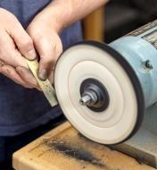 Personne polissant un pied à coulisse en laiton avec un disque à polir en tissu