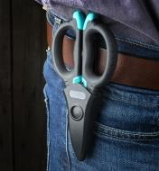 A pair of electrician scissors being carried in the included belt sheath worn on a hip