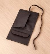 A leather cord wallet spread open on a tabletop