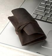 A leather cord wallet on a laptop computer, cinched closed with its leather tie