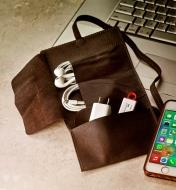 A cord wallet beside a laptop and smartphone, holding a charge cable, ear buds and a flash drive