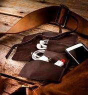 A cord wallet beside a smartphone and purse, holding a charge cable, ear buds and a flash drive