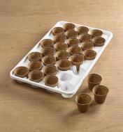 Plateau auto-irrigant pour semis à côté de trois pots retirés sur une table
