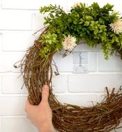 A wreath is hung on a brick wall with a brick clamp that is painted to match the wall