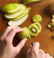 Slicing a kiwi fruit with the serrated paring knife