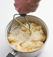 Mashing potatoes in a pot with the potato masher