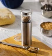 Nutmeg grinder on a cutting board with a measuring spoon of ground nutmeg