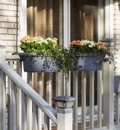 A pair of Fence and Railing Planters mounted on a porch railing