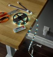 An LED tape light kit laid out on a table, plugged into an outlet to test it before installation
