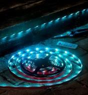 Ensemble de luminaire-ruban à DEL partiellement installé sous une marche d'un escalier extérieur et diffusant une lumière bleue