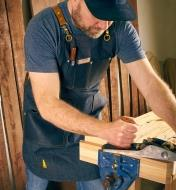 A man planing a board while wearing the All-Purpose Apron