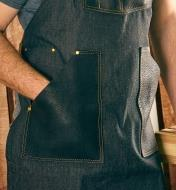 A hand in one of the All-Purpose Apron's lap pockets