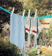 A pair of socks and a towel held on a clothesline with Grandma's Clothespins
